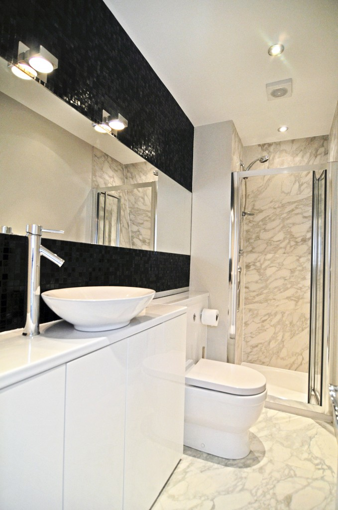the bespoke hand made bathroom units mean that the room has a sleek look but still has ample storage ample shower room